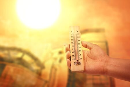 Hand holding thermometer with high temperature on the city with glowing sun background. Heatwave concept Stock Photo