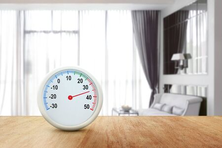 The thermometer on a wooden table measuring the temperature inside the home. Heatwave concept