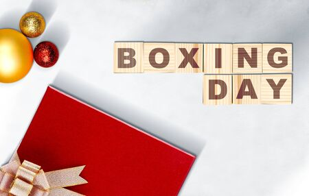 Gift box with a ribbon and Christmas ornament with Boxing Day text on a wooden cube with floor background Stock Photo
