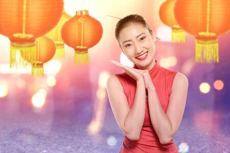 Asian Chinese woman in a cheongsam dress celebrates Chinese New Year. Happy Chinese New Year
