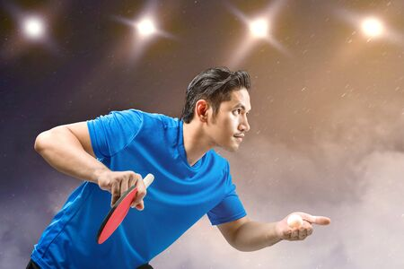 Asian table tennis player man serving the ball with spotlights background