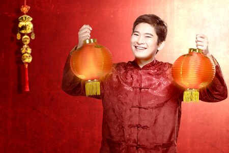 An Asian Chinese man in a cheongsam dress holding Chinese lantern. Happy Chinese New Year