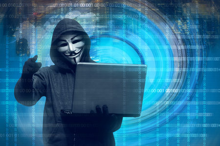 Hooded man with mask holding laptop against binary code in background Editorial