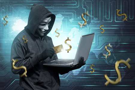 Hacker man with mask holding credit card with laptop on his hand on digital background