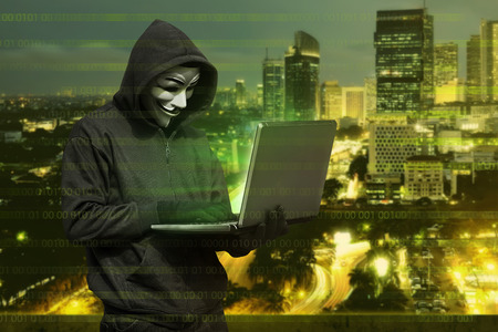 Hacker man with mask typing on laptop against modern city background