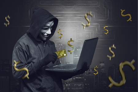 Hooded man wearing anonymous mask and holding laptop while showing credit card against modern city shadow background