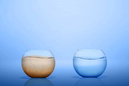 The empty fishbowl with freshwater and dirty water on blue background