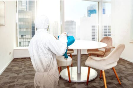 Man in a white protective suit spraying disinfectant in the office room. Prevent the spread flu disease Coronavirus