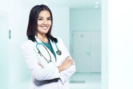 Asiatische Arztfrau mit Stethoskop, die im Krankenhaus steht