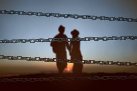 Chain fence with the silhouette of a couple standing in the morning. World Refugee Day Concept