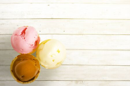 Ice cream of chocolate, vanilla, and strawberry with wooden table background
