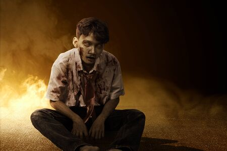 Scary zombie with blood and wound on his body sitting on the floor with smoke background Stock Photo