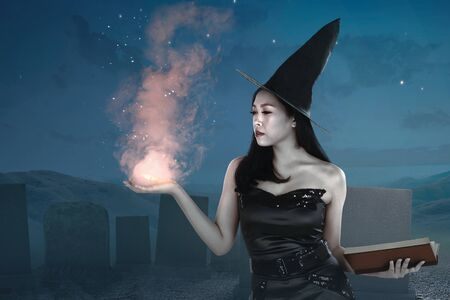 Asian witch woman with spellbook showing magic on her hand on the graveyard Standard-Bild