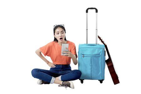 Femme asiatique assise avec une valise tenant un téléphone portable isolé sur fond blanc