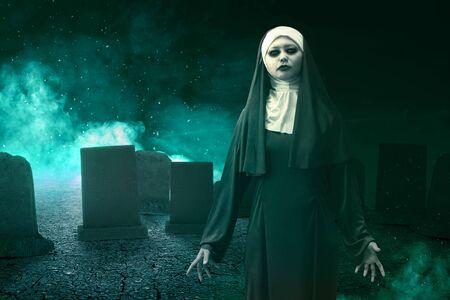 Nonne du diable effrayante debout avec un feu mystique sur le cimetière. Notion d'Halloween Banque d'images