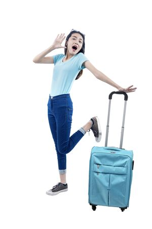 Asian woman standing with suitcase isolated over white background