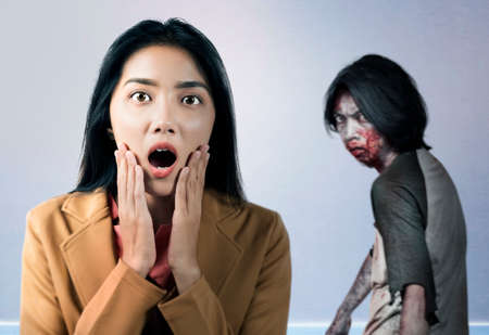 Asian businesswoman scared looking at zombies inside the building. Halloween concept