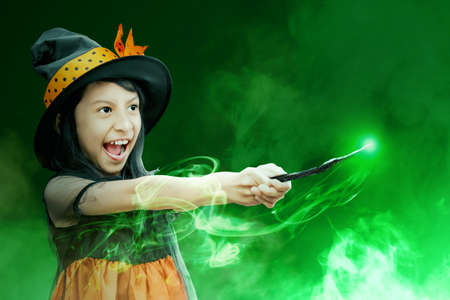 Asian witch little girl using the wand with a magic shine with mystical fire on black background Stock fotó - 150636233