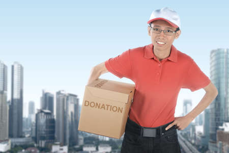 Asian man carrying box with donation text to collecting donations in the city