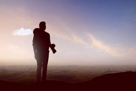 Silhouette of a man with a backpack holding the camera on the top of the hills. World Photography Day