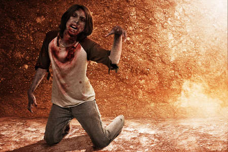 Scary zombie with blood and wound on his body crawling on the floor with a dirty wall background