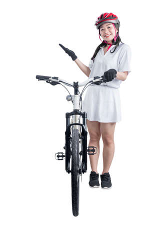 Asian woman with a bicycle helmet standing beside her bicycle isolated over white background