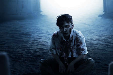 Scary zombie with blood and wound on his body sitting on the graveyard