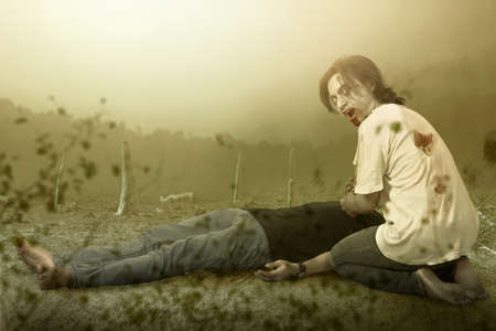 Scary zombie with blood and wound on his body eating a dead man on the field