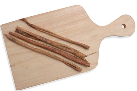 Cinnamon sticks on cutting board isolated over white background