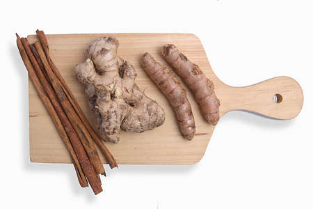 Fresh turmeric and ginger with cinnamon sticks on cutting board isolated over white background