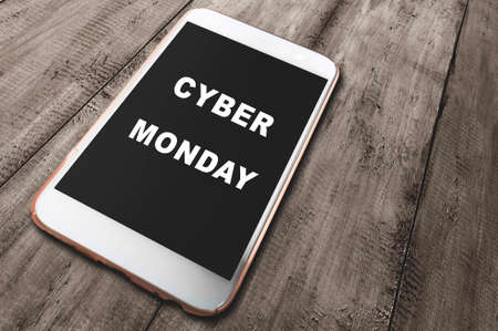Cyber Monday text on the mobile phone screen with a wooden background. Cyber Monday concept