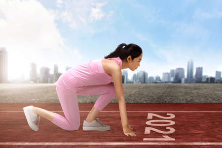 Asian runner woman ready to run on the 2021 line. Happy New Year 2021 Stock fotó