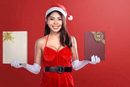 Asian woman in Santa costume holding gift box with red background