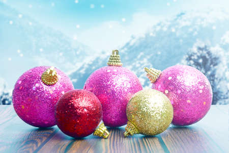 Colorful Christmas ball on wooden table with snowfall background. Merry Christmas