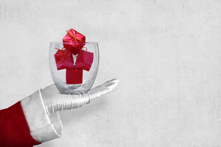 Santa Claus showing Christmas decoration in glass bowl with white wall background Archivio Fotografico
