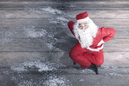 Asian man in Santa costume sitting on wooden floor. Merry Christmas