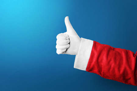 Santa Claus hand showing thumbs up gesture with a colored background. Merry Christmas