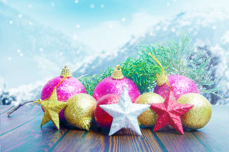 Christmas decorations with colorful ornaments on wooden table with snowfall background. Merry Christmas