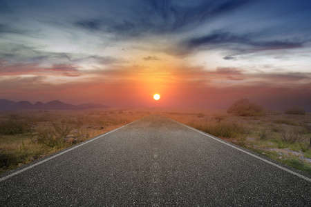 Asphalt road with green grass and sunrise sky background