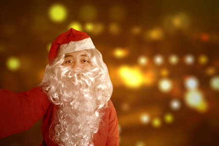 Asian man in Santa costume taking a selfie with a blurred light background. Merry Christmas