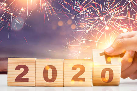 Hand changes the wooden cube from 2020 to 2021. Happy New Year 2021