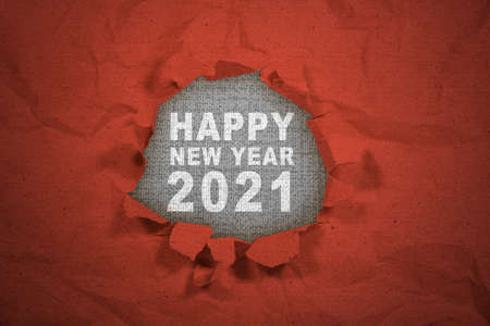 A ripped paper showing 2021 with a gray background. Happy New Year 2021