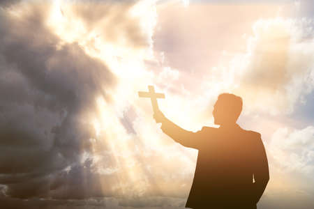 Silhouette of a businessman holding Christian cross with a dramatic sky background