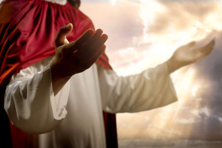 Jesus Christ praying to god with a dramatic sky background