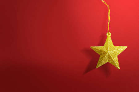Golden Christmas ornament hanging with a colored background. Merry Christmas