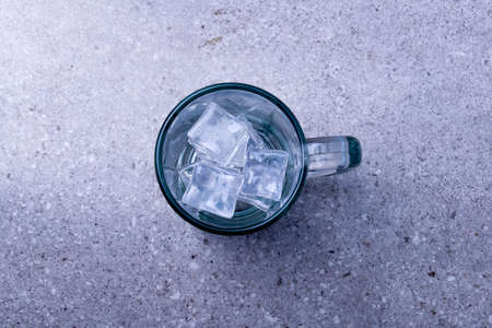 Empty glass with an ice cube on the desk