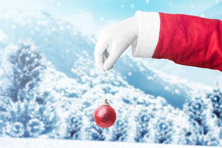 Santa Claus hand holding Christmas ball with snowfall background. Merry Christmas