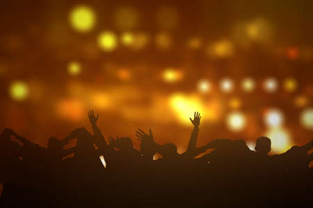 The crowd of people raised hands together with blurred light background