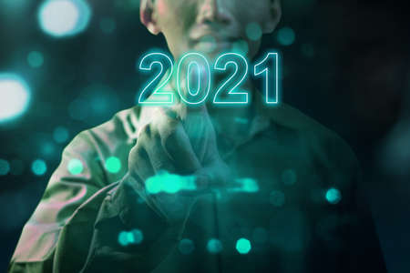 Businessman hand touching the virtual screen of 2021. Happy New Year 2021