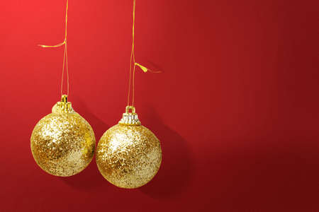 Golden Christmas ball hanging with a colored background. Merry Christmas